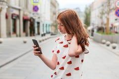 走和使用一个巧妙的电话的时尚愉快的女孩的正面图 免版税库存照片