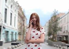 走和使用一个巧妙的电话的时尚愉快的女孩的正面图 图库摄影