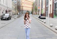 走和使用一聪明的pho的时尚愉快的女孩的正面图 免版税库存照片