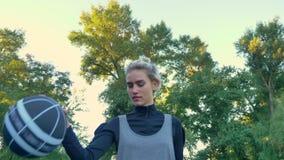 走和使用与球,有上面蓝天的公园的迷人的女性蓝球运动员在背景,低角度中 股票视频