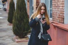 走和使用在城市街道上的时尚愉快的妇女的正面图一个巧妙的电话 库存图片