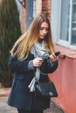 走和使用在城市街道上的时尚愉快的妇女的正面图一个巧妙的电话 免版税库存照片