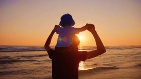 走和使用在海滩的母亲和小儿子在日落 股票录像