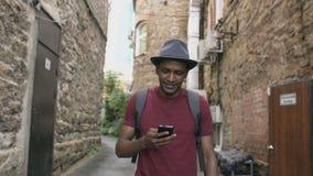 走和使用智能手机app的愉快的非裔美国人的学生户外 股票录像