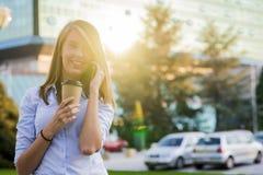 走和写或者读sms消息的愉快的美丽的妇女 免版税库存图片