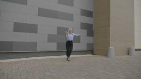 走和在一个滑稽的自由式拉丁美州的舞蹈的节奏的后年轻优美的女实业家公开用她的方式工作- 股票视频