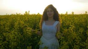 走和微笑在油菜花田的十几岁的女孩对日落 股票视频