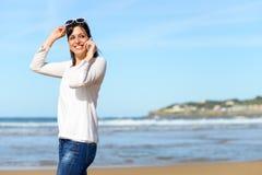 走和拜访手机的妇女 免版税库存照片