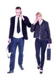 走和拜访移动电话的商人。 免版税库存图片