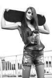 走和拿着滑板的美丽的少妇 免版税库存图片