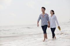 走和握手的年轻夫妇由水在海滩,中国渐近 图库摄影