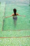 走和放松在游泳池的亚裔女孩 免版税库存照片