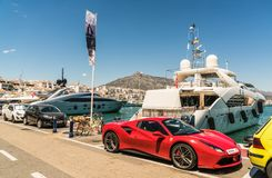 走和看大豪华游艇和法拉利的游人在港口 免版税库存图片