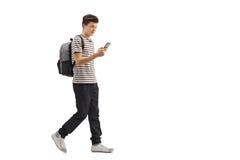 走和看电话的少年学生 免版税图库摄影