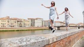 走和跳跃沿遏制的两名年轻笑的妇女由河 股票视频