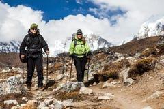 走和远足在喜马拉雅山的夫妇 图库摄影