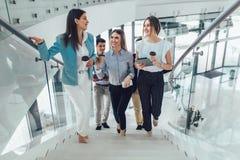 走和采取在办公楼的商人和女实业家台阶 图库摄影