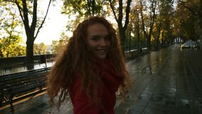 走在一个五颜六色的秋天公园的年轻白种人妇女由湿胡同,享用秋天叶子,转过来快乐 影视素材