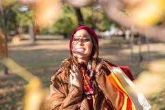 走在一个公园的美丽的少妇在秋天在购物以后 免版税库存图片
