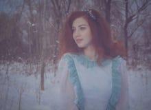 走在一个冷的冬天森林的红发女孩 免版税库存照片