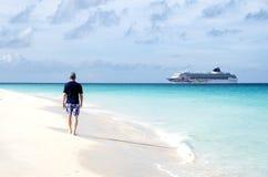 走在一个加勒比海滩和看游轮的后面观点的一个人 免版税库存照片