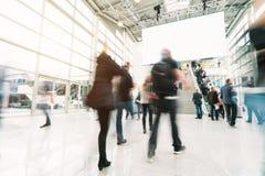 走在一个商品交易会大厅里的被弄脏的人民 免版税图库摄影