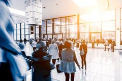 走在一个商品交易会大厅里的被弄脏的人民 免版税库存图片