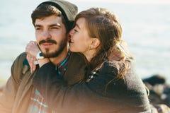 走在一个多岩石的海滩的美好和时髦的夫妇 夫妇博士 免版税库存图片