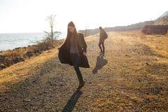 走在一个多岩石的海滩的美好和时髦的夫妇 夫妇在夹克、帽子和起动穿戴了 免版税库存照片