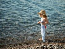 走在一个有卵石花纹的海滩的小女孩 免版税图库摄影