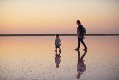 走在一个桃红色湖的盐和盐水的母亲和孩子,上色被微藻类Dunaliella盐沼 库存照片