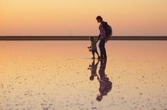 走在一个桃红色湖的盐和盐水的母亲和孩子,上色被微藻类Dunaliella盐沼 图库摄影