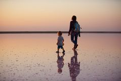 走在一个桃红色湖的盐和盐水的母亲和孩子,上色被微藻类Dunaliella盐沼 免版税库存照片