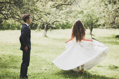 走在一个植物的公园的愉快的婚礼夫妇 图库摄影