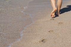 走在一个沙滩的夫人 库存照片