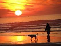 走在一个海滩的妇女&狗Siluette有日落背景 免版税图库摄影