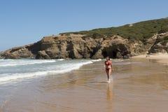 走在一个海滩的美丽的妇女在红色比基尼泳装的阿尔加威葡萄牙在度假 免版税图库摄影