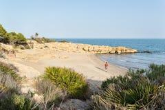 走在一个田园诗地中海海滩的年轻人在日落 图库摄影