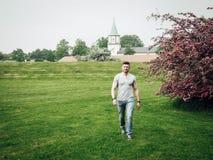 走在一个绿色领域的英俊的人在开花的树附近 库存照片