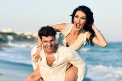 走在一个美丽的海滩的年轻愉快的夫妇 免版税库存图片