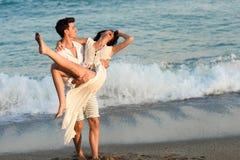 走在一个美丽的海滩的年轻愉快的夫妇 图库摄影