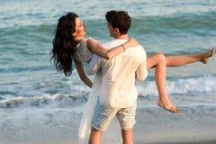走在一个美丽的海滩的年轻愉快的夫妇 免版税库存照片