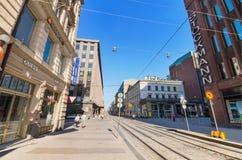 走在一个晴天的人们,在一条典型的街道在赫尔辛基的中心6月的, 24 2013年 免版税库存图片