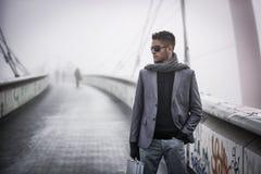 走在一座桥梁的英俊的时髦人在冬天 免版税库存照片