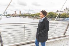 走在一座桥梁的年轻混合的族种妇女在伦敦 库存照片