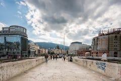 走在一座石桥梁的人们在斯科普里的市中心 免版税库存照片