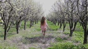 走在一开花的庭院和休息的白肤金发的女孩 影视素材