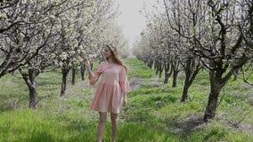 走在一开花的庭院和休息的白肤金发的女孩 股票录像