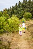 走在一条偏僻的道路的男孩和女孩 库存照片