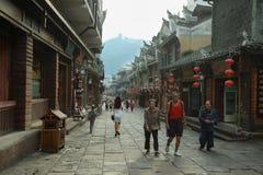 走在一条商业街的人们在凤凰牌古镇  库存照片